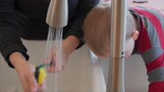 Boy plays while mother cleans the dishes Stock Footage