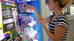Young Woman Chooses Make-up Foundation at Cosmetics Shop Stock Footage