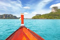 Wooden boat and a tropical island in distance. - stock photo