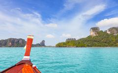 Wooden boat and a tropical island in distance. Stock Photos