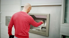 4K suspicious man taking cash from an ATM machine - stock footage