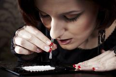 Beautiful woman snorting drugs Stock Photos