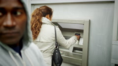 Stock Video Footage of 4K Suspicious character waits behind a woman as she takes money from ATM machine