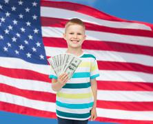 Smiling boy holding dollar cash money in his hand Stock Photos