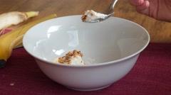 Person eats healthy breakfast of banana and granola Stock Footage