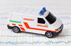 Toy ambulance car on ecg - stock photo