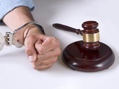 A hand handcuffed next to a gavel - stock photo