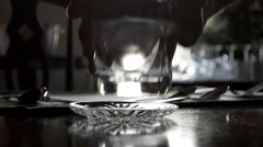 Man Placing Water Glass on Mahoganey Stock Footage