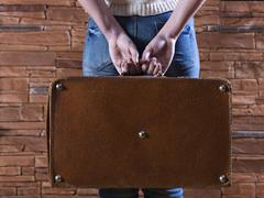 holding an old suitcase - stock photo