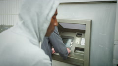 4K Suspicious character waits behind a man as he takes money from an ATM machine Stock Footage