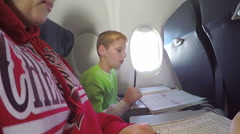 Young boy on airplane doing school work closes shade on window Stock Footage