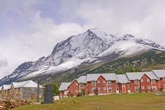 Alpine Lodge beneath Snowy Mountains - stock photo