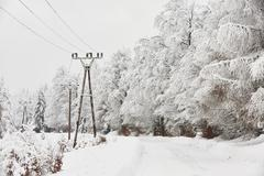 Snow covered electricity pylons in wintry landscape Stock Photos