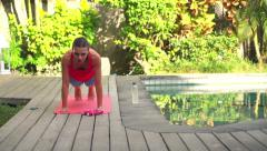 Young woman doing plank exercise on mat in garden by swimming pool HD Stock Footage
