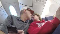 Husband and wife kiss on airplane Stock Footage