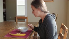 A woman eats a healthy breakfast of banana and granola Stock Footage