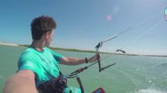 Kiter kiteboarding in sunny flat lagoon Stock Footage