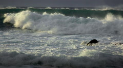 Big waves roll into a beach following a big storm in slow motion. Stock Footage