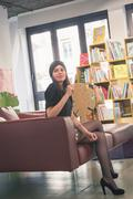 Beautiful young brunette posing in a bookstore - stock photo