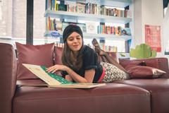 Beautiful young brunette reading book in a bookstore Stock Photos