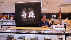 Salesperson welcomes customers in retail shop in Kyoto, Japan - stock footage