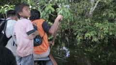 Natives on a boat on the Amazon reach the shore Stock Footage