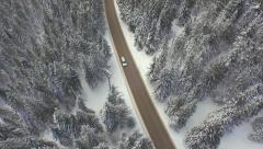 AERIAL: Car driving along the forest road in winter Stock Footage