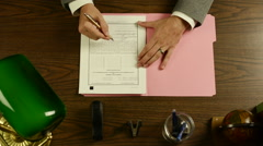 SIGNING DOCUMENT AT DESK Stock Footage