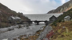 View of the Caban Coch dam with turbine houses and bridge in the foreground - stock footage