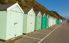 Light green beach huts traditional English seaside structure - stock photo