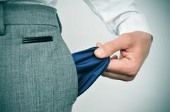 broke businessman showing his empty pocket - stock photo