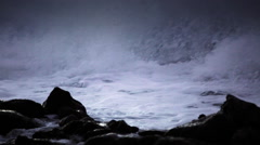 Water level view of waves crashing and rolling into a rocky shore in slow Stock Footage