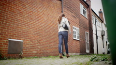 4K Woman walking alone through street is attacked by hooded thugs - stock footage
