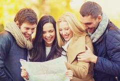 couples with tourist map in autumn park - stock photo