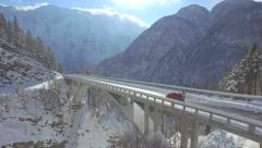 AERIAL: Car drives across mountain viaduct Stock Footage