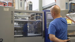 Man operating injection moulding machine Stock Footage