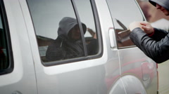 4K Hooded street criminal uses screwdriver to break into a car - stock footage