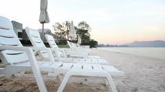White sunbeds and umbrella on the beach in Thailand, Dolly shot Stock Footage