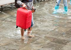 Asian tourist barefoot in the water with her luggage. Venice, Italy. Stock Photos