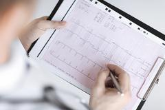 Stock Photo of male doctor hands with cardiogram