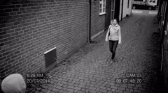 4K CCTV footage of woman in street being attacked by hooded thugs Stock Footage