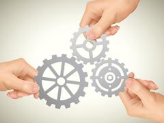 Cooperation concept: hands holding gears Stock Illustration