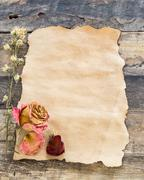 Old-paper with dried rose on a wooden background Stock Photos