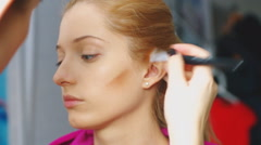 Makeup artist is applying tonal powder to the face of a beautiful caucasian Stock Footage