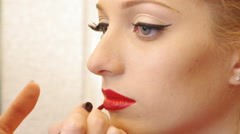 Closeup view to the professional makeup artist is applying red lip gloss to a - stock footage