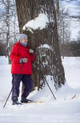 Woman retirement age, walking in winter forest - stock photo