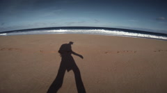 A man's shadow walks along a beach with a backpack. Stock Footage
