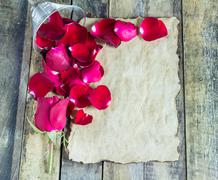 Fresh red rose and old paper on a wooden background - stock photo