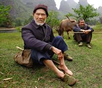 YANGSHUO COUNTY, GUANGXI, CHINA - MARCH 29: Elderly Chinese shepherds in gree Stock Photos