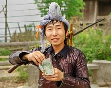 GUIZHOU PROVINCE; CHINA - APRIL 10: Man Miao ethnic group, with a musket on h - stock photo